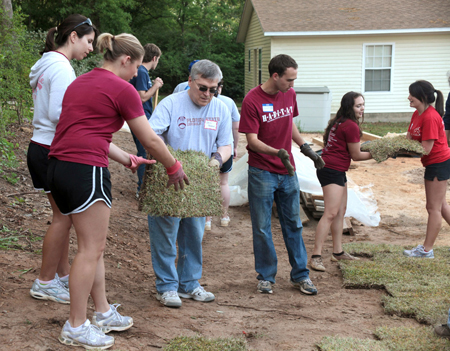 President Barron helping to lay sod along with FSU students volunteering at a recent Habitat for Humanity build.