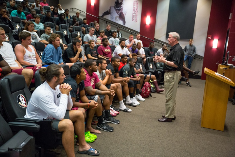 President John Thrasher meets with members of the football team Monday.