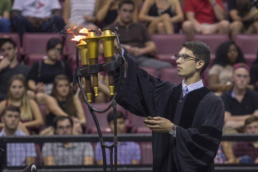 FSU Sophomore, Gabriel Loring lights the torches.