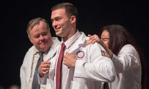 Nicholas Casler is coated by his mother, Dr. Alix Casler, at the College of Medicine's White Coat Ceremony Friday, Aug. 12.
