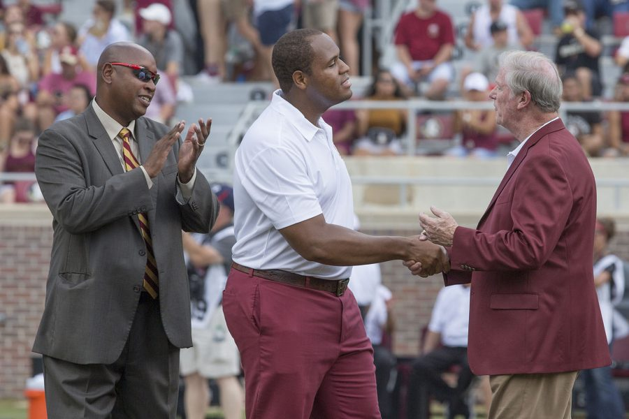 FSU President John Thrasher shakes hands with NCAA shot put champion and Rhodes Scholar recipient Garrett Johnson as FSU Athletics Director Stan Wilcox looks on. Johnson was inducted into the FSU Athletics Hall of Fame this weekend.