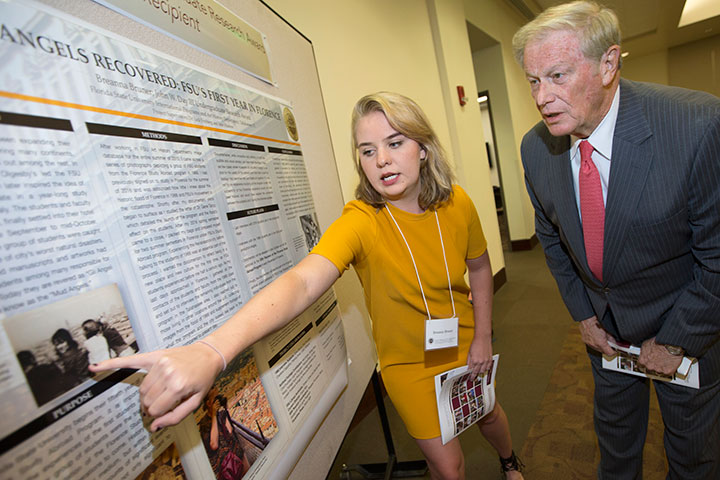 Breanna Bruner, winner of the John W. Day III Undergraduate Research Award, shows off her research to President Thrasher.