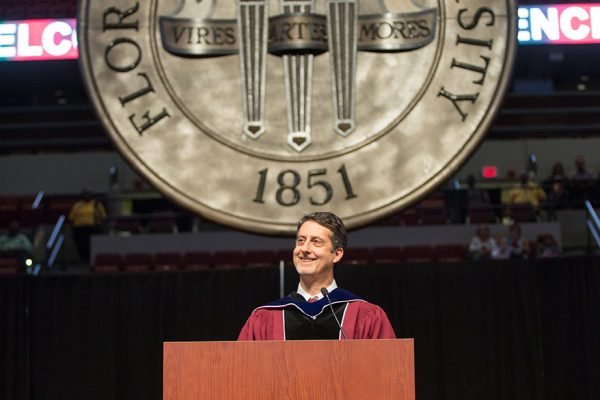 FSU Professor Joseph Schlenoff addresses graduates in front of a new decorative seal created by the FSU Master Craftsmen Studio. It will be displayed at all future commencement ceremonies.
