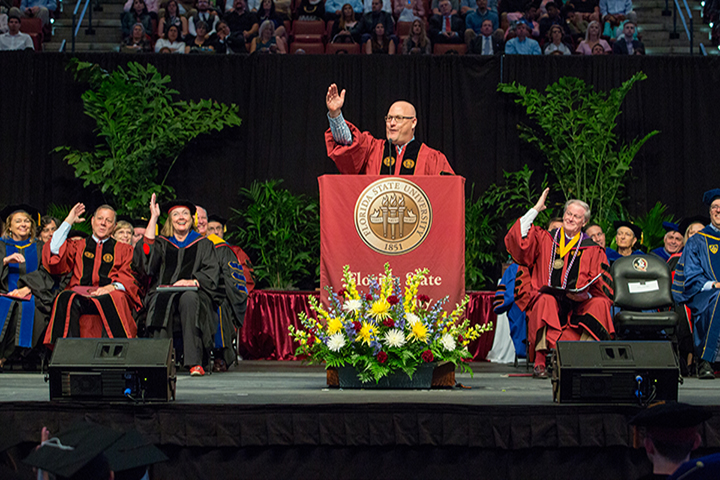 Alumnus Michael Goldberg leads the Saturday morning's commencement crowd in the war chant.