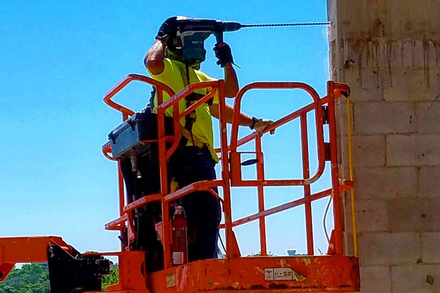 Marc Hamilton handles an oversized Makita drill equipped with a 22-inch bit to bore holes in concrete walls that will support an east-facing bank of windows stretching from the ground to the top of the building.