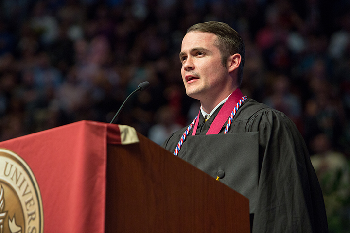 Student-veteran Ryan Taylor leads the crowd in the Pledge of Allegiance at Friday night's commencement ceremony.