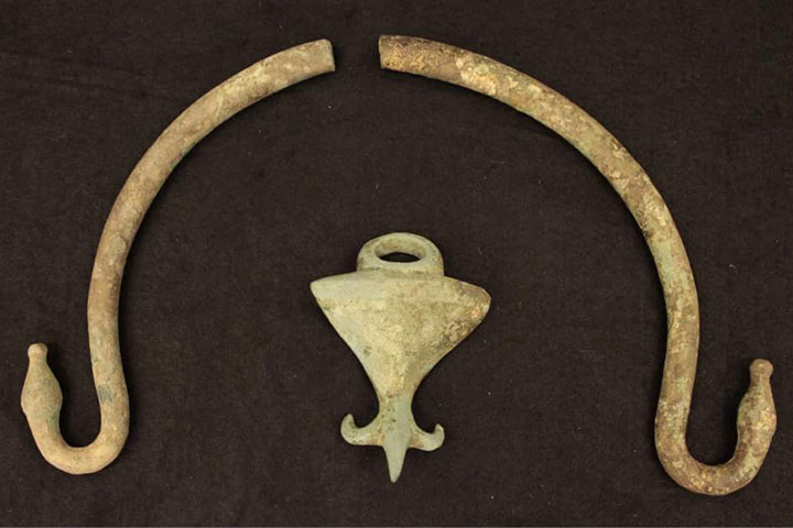 "A bronze handle with animal head finials and a ""fleur-de-lis"" handle attachment from the Florida State University-operated archaeological site Cetamura del Chianti."