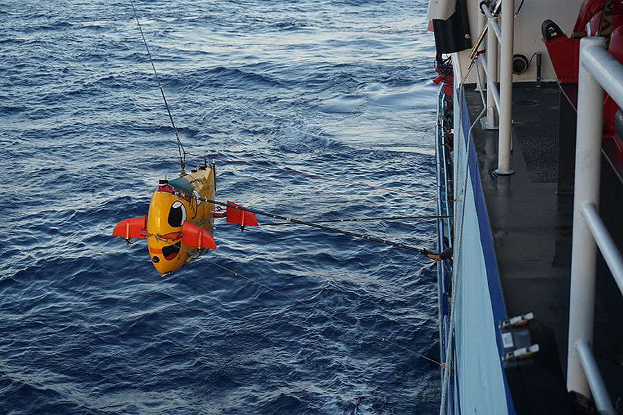 The autonomous underwater vehicle Sentry lowered from a research ship; it will explore deep reefs. (Photo: Nicole Morgan)