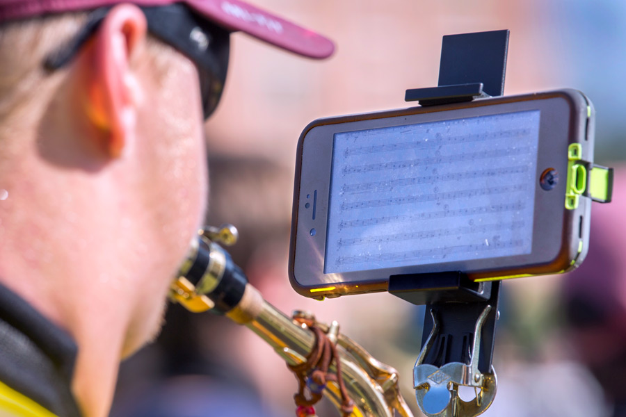 """The Marching Chiefs are using the """"eFlip"""" attachment, which allows them to follow their song music on a smartphone instead of printed sheets."""