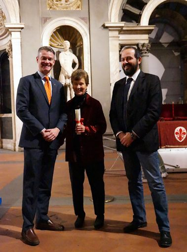 Nancy de Grummond is congratulated by the U.S. consul general to Florence, Benjamin Wohlauer (left), and the mayor of Gaiole in Chianti, Michele Pescini.