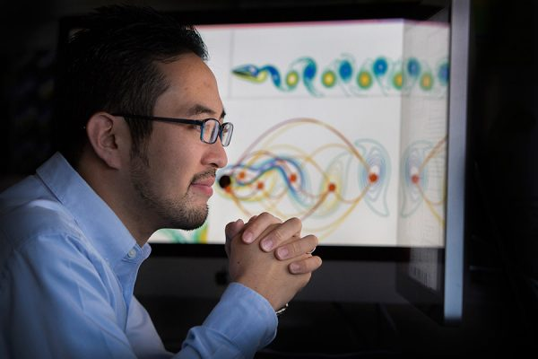 Assistant Professor of Mechanical Engineering Kunihiko (Sam) Taira reviews data in his lab.
