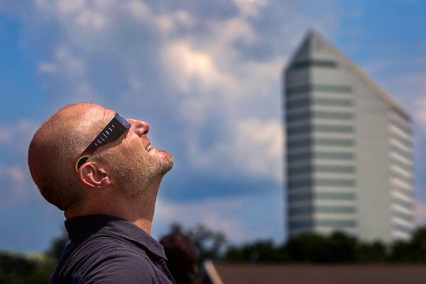 During the 2017 solar eclipse, Jim Moran School of Entrepreneurship's Entrepreneur in Residence Mark McNees views the event from atop the Turnbull Center parking deck.