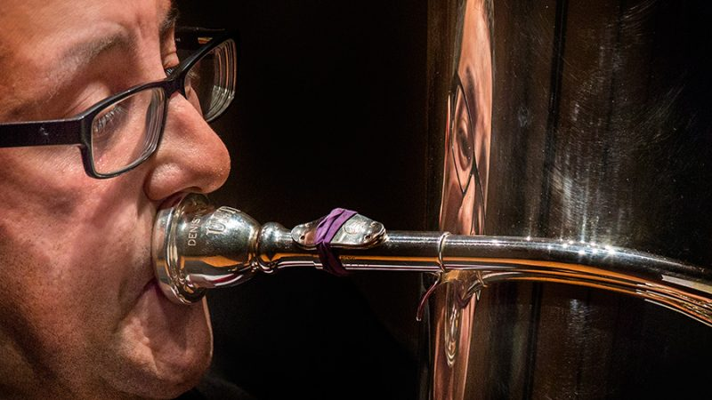 Justin Benavidez, assistant professor of Tuba and Euphonium, is reflected in his instrument during his faculty recital.