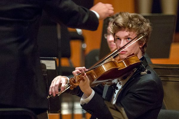 A violinist keeps his eye on the conductor during a University Philharmonia performance.
