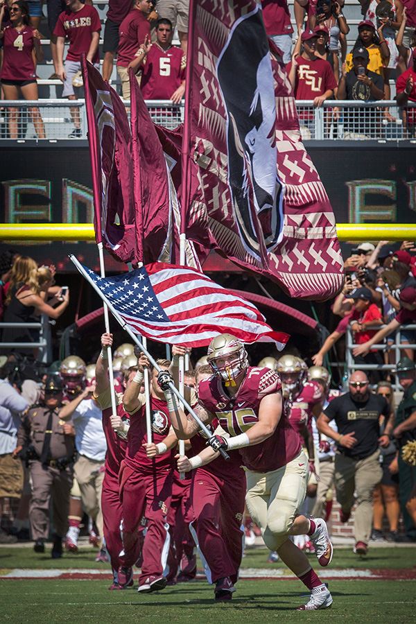 The Florida State University Seminoles take the field with the American flag during pregame of the Veterans Appreciation game.
