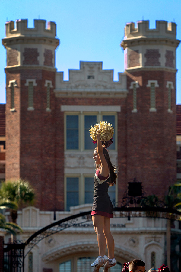 A Florida State University cheerleader is held in the air with the Westcott building as a backdrop during the annual Homecoming Parade.