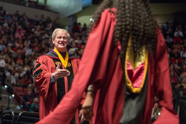 President Thrasher congratulates graduates as they walk on stage at fall commencement. (FSU Photography Services)