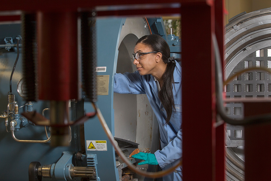 Graduate student Roslyn Shanklin examines the autoclave at the High-Performance Materials Institute.