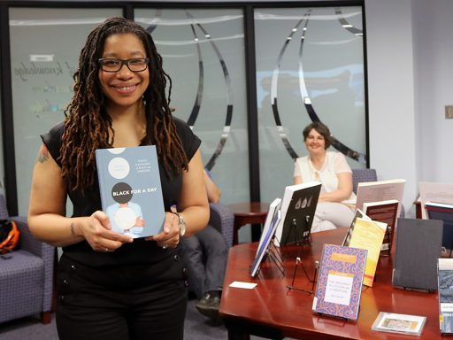 "Associate Professor of English Alisha Gaines with her book ""Black for a Day: White Fantasies of Race and Empathy."" (Photo: University Communications)"