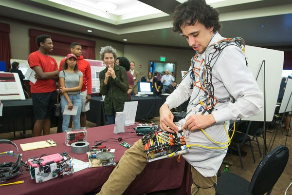 Lucas von Hollen of FSU's School of Information configures his robot suit, which was crafted entirely of recycled and found materials.