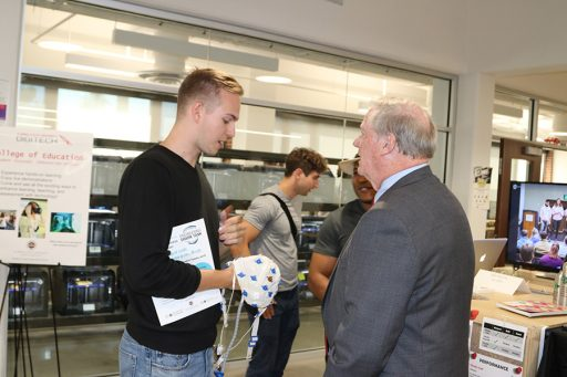 Junior Alex Koberda explains his idea to use an EEG cap to test witness validity to President John Thrasher. (Photo: Univesity Communications)