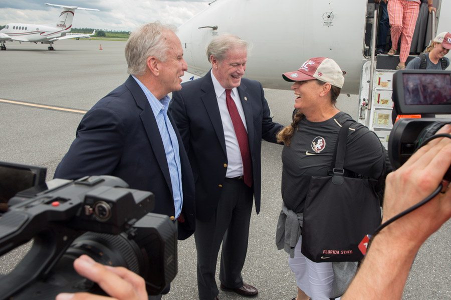 Chairman of the FSU Board of Trustees Ed Burr and President John Thrasher greet softball Coach Lonni Alameda at Tallahassee International Airport on June 6, 2018, following the team's victory at the 2018 Women's College World Series in Oklahoma City. (FSU Photography Services)