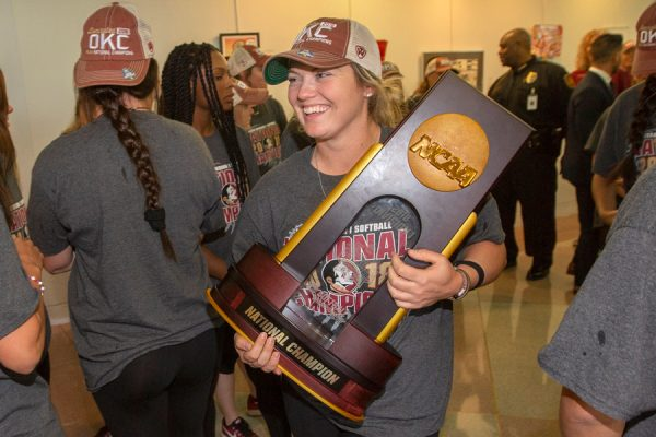 FSU senior Jessie Warren carries the 2018 NCAA Softball National Championship trophy into Tallahassee City Hall, where the team was honored by city commissioners on June 6, 2018. (FSU Photography Services)