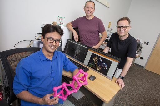 Doctoral student Kevin Ryan (seated) developed a machine learning model to predict new chemical compounds. Standing are Professor Michael Shatruk (left) and graduate student Jeff Lengyel (right).