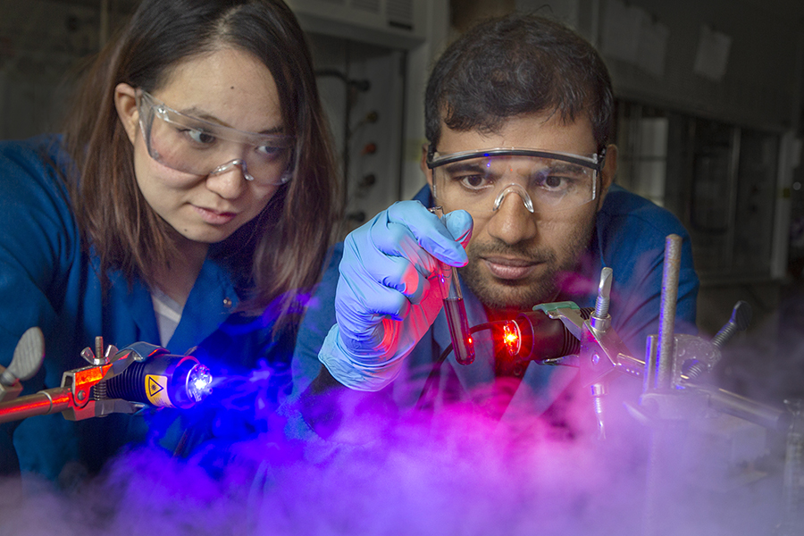 Graduate student Yan Zhou (left) and postdoctoral researcher Sahan Salpage use light to separate metal ions. This process, scientists believe, will be cheaper and greener than existing methods. (FSU Photography Services)