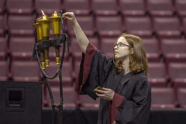 A student lights a torch during FSU New Student Convocation Sunday, Aug. 26, 2018. (FSU Photography Services)