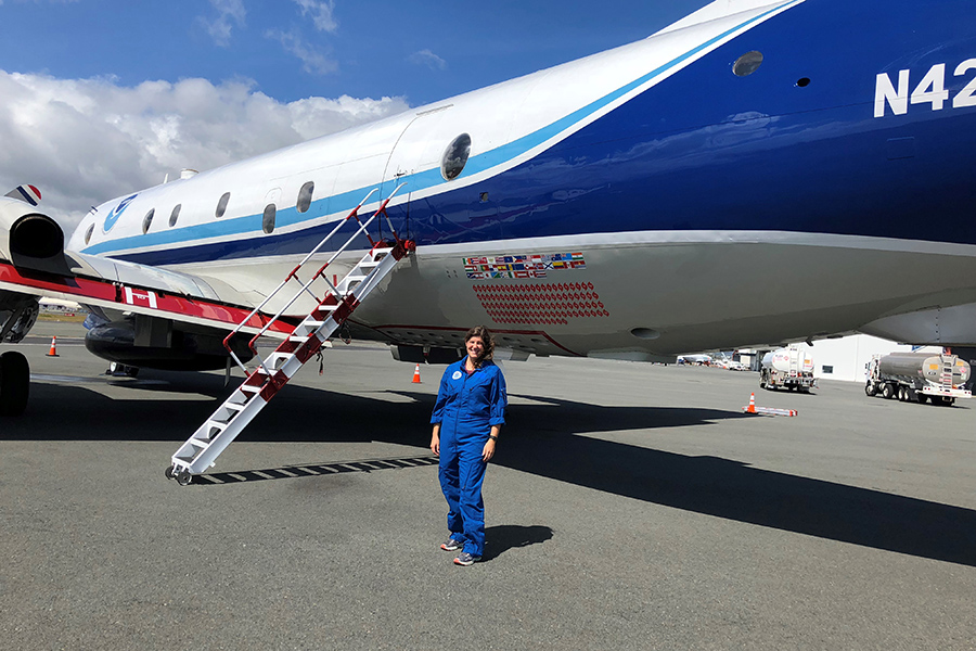 FSU postdoctoral researcher Heather Holbach poses in front of a NOAA WP-3D research plane, which is specially outfitted for hurricane hunting.