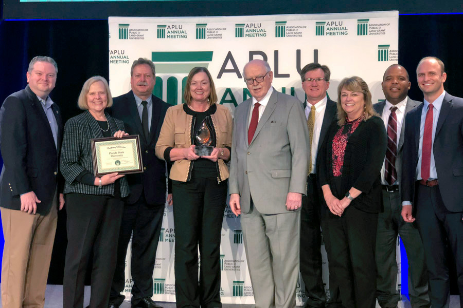 Provost and Executive Vice President for Academic Affairs Sally McRorie, along with a team of FSU leaders, accepts the prestigious national award from APLU President Peter McPherson.