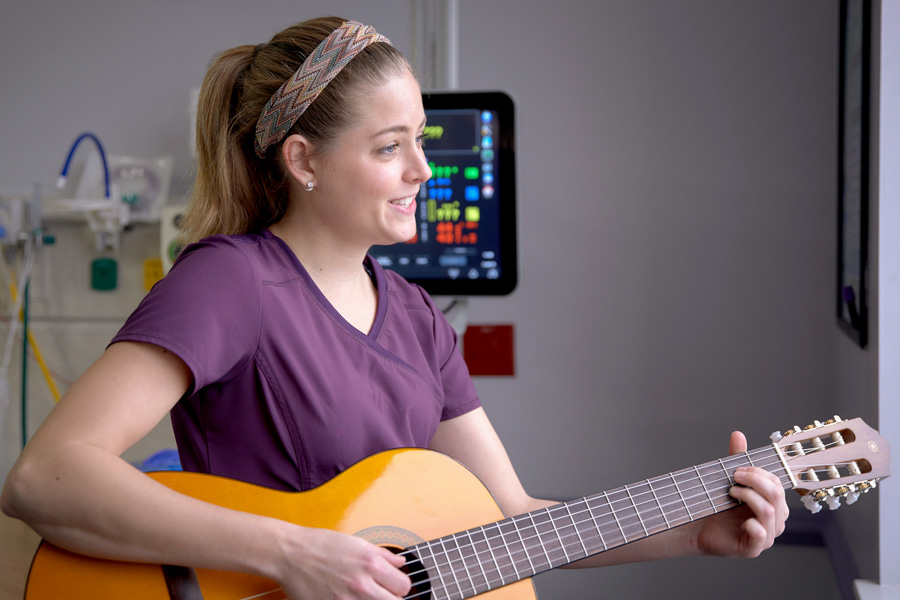 "Ciele Gutierrez offers music therapy by singing or strumming a guitar. ""I provide A cappella singing music,"" she said. ""We use lullabies in the NICU because they are not complex, they're repetitive, easy to listen to, and they're already promoting language development."" (Photo: Tallahassee Memorial HealthCare)"