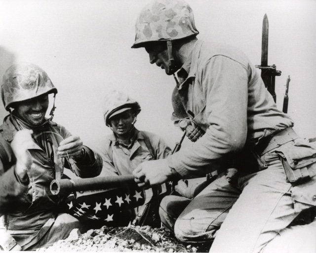 "Ernest ""Boots"" Thomas, a former resident of North Florida, ties the first flag to a pipe that would be used as flag pole for the first American flag raised in Iwo Jima. Marines from 3rd Platoon, Company E, 2nd Battalion, 28th Marine Regiment raised a fifty-four by twenty-eight inch flag during the Battle of Iwo Jima. Because this flag proved too small to clearly see from the ground 546 feet below, a second flag measuring eight by four feet replaced the first one that is now famously depicted in Joe Rosenthal's photograph."