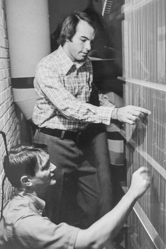 """In 1975, FSU's Michael Corzine (standing), at the time an assistant professor of organ, consulted with organ builder Walter Holtkamp Jr. on the design of a new pipe organ for Opperman Music Hall. Here, they check the Holtkamp organ's """"trackers,"""" which connect keys and pedals to the pipe's vales. (Photo: Michael Corzine)"""