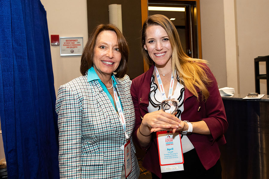 Nancy Roman, president and CEO of Partnership for a Healthier America, presents April Lovett, strategic planning and assessment analyst at FSU, with a crystal apple in recognition of Florida State University meeting PHA's Healthier Campus Initiative guidelines.