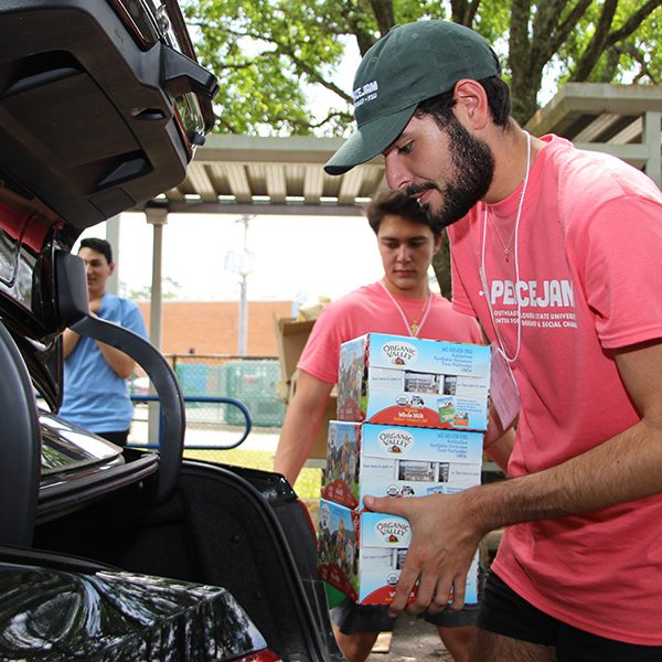 Students load cartons of milk and juice into a resident's car while working with FarmShare to distribute meals to the community at Sabal Palm Elementary School on April 6, 2019.