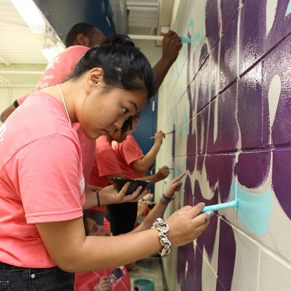 PeaceJam Southeast Conference attendees paint a mural in the P.E. room at Sabal Palm Elementary School on April 6, 2019.