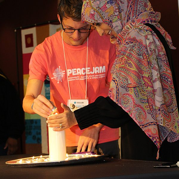 A student lights a candle with the flame from Nobel Peace Laureate Tawakkol Karman after telling the PeaceJam Southeast Conference what inspires him on April 7, 2019.
