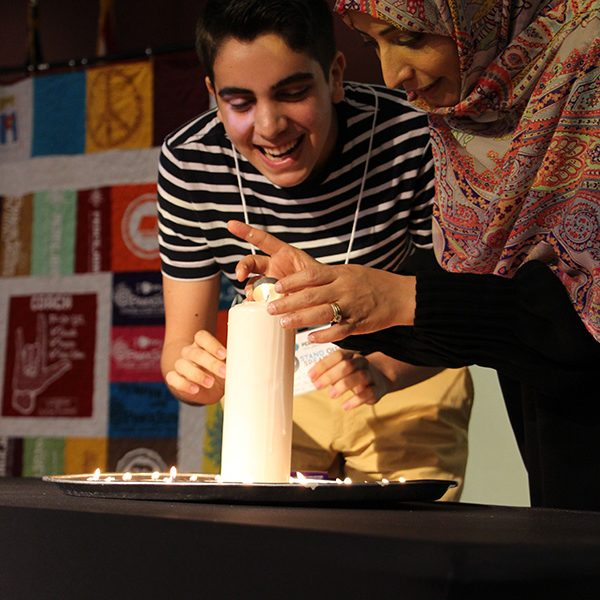 Nobel Peace Laureate Tawakkol Karman helps a student light a candle during the Ceremony of Inspiration at the PeaceJam Southeast Conference on April 7, 2019.