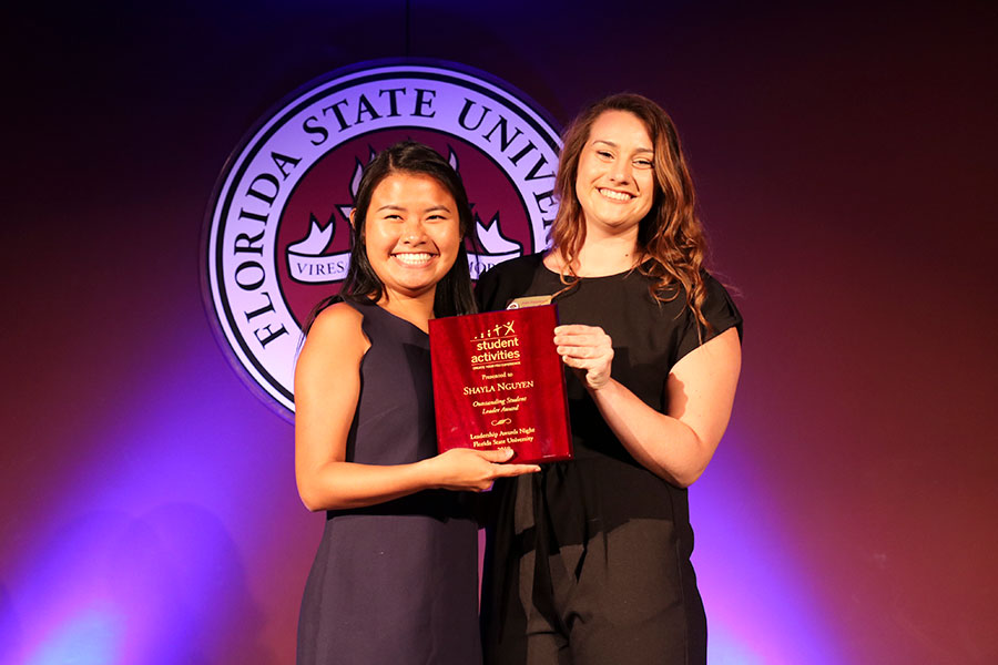 Shayla Nguyen accepts an Outstanding Student Leader Award from Student Program Coordinator Julie Fleishman at the Leadership Awards Night April 9, 2019. (Photo: Division of Student Affairs)
