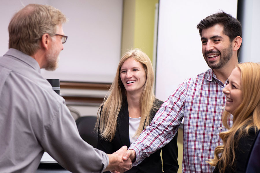 Steve McClellan, from left, principal data scientist at Integrated Musculoskeletal Care, Inc. visits with Master of Science in Business Analytics (MS-BA) students Bryce Shay, Zachary Anders and Kellie Nielson before their final class presentation. Each student team was tasked with exploring IMC data and developing a business project to tackle and present.