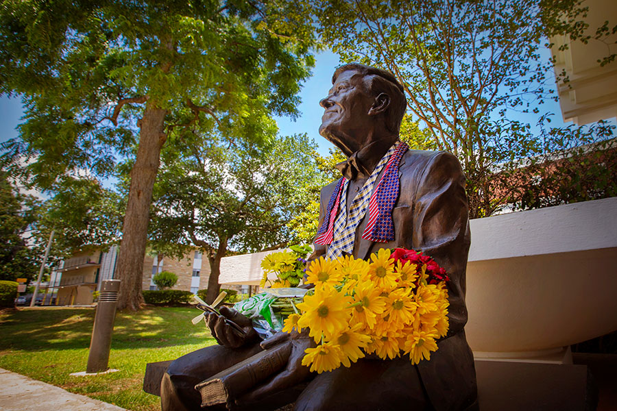 Flowers and bowties are left in tribute of President Emeritus Sandy D'Alemberte at his statue outside the College of Law May 21, 2019. (FSU Photography Services)