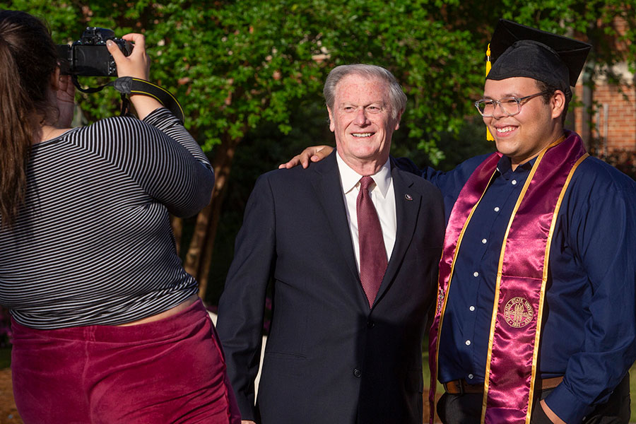 FSU President John Thrasher stops to take a picture with a graduating student. (FSU Photography Services)