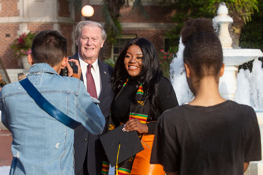 FSU President John Thrasher poses for a photo with a graduating student. (FSU Photography Services)