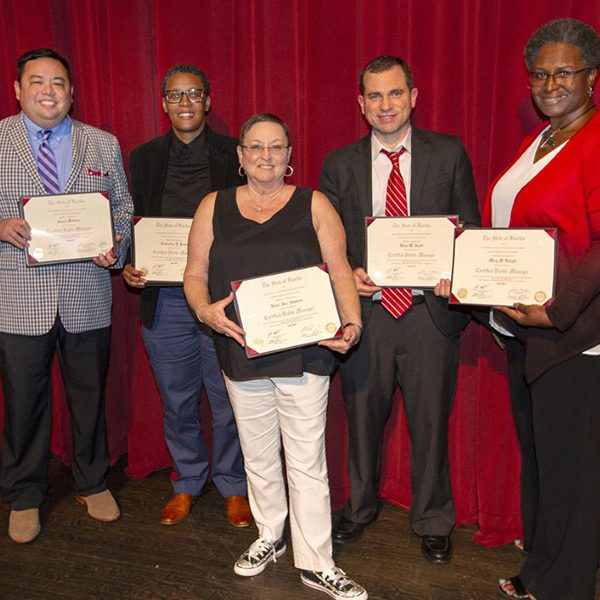 A group of graduates from the Florida Certified Public Manager (CPM) program poses with their certificates after the July 18 ceremony at Ruby Diamond concert hall. (FSU Photography Services)