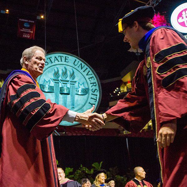 President John Thrasher congratulates a graduate during FSU's 2019 summer commencement. (FSU Photography Services)