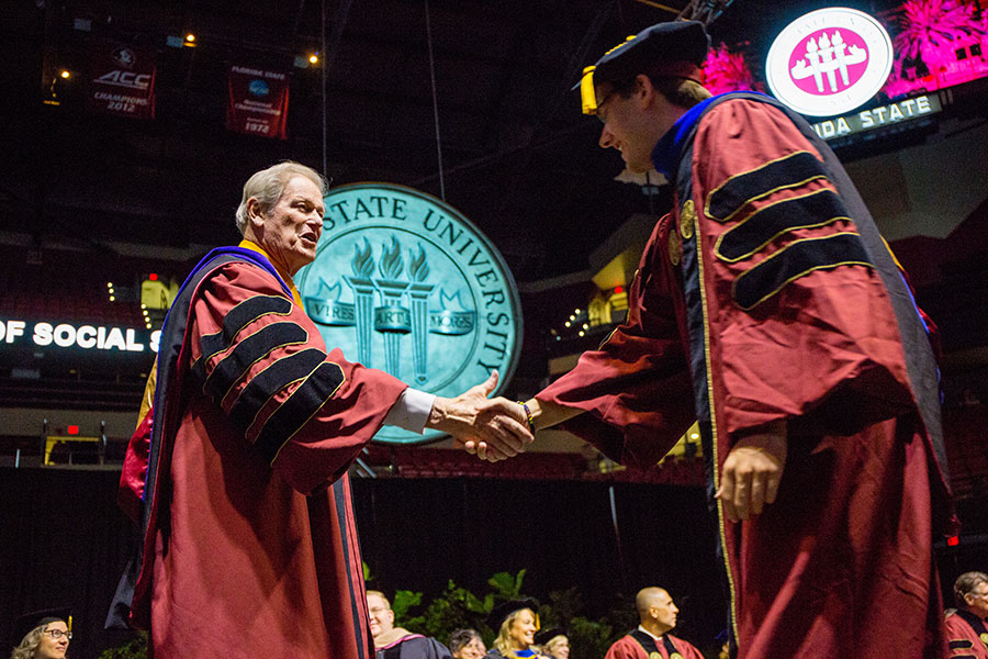President John Thrasher congratulates a graduate during FSU's 2019 summer commencement. (FSU Photography Services)