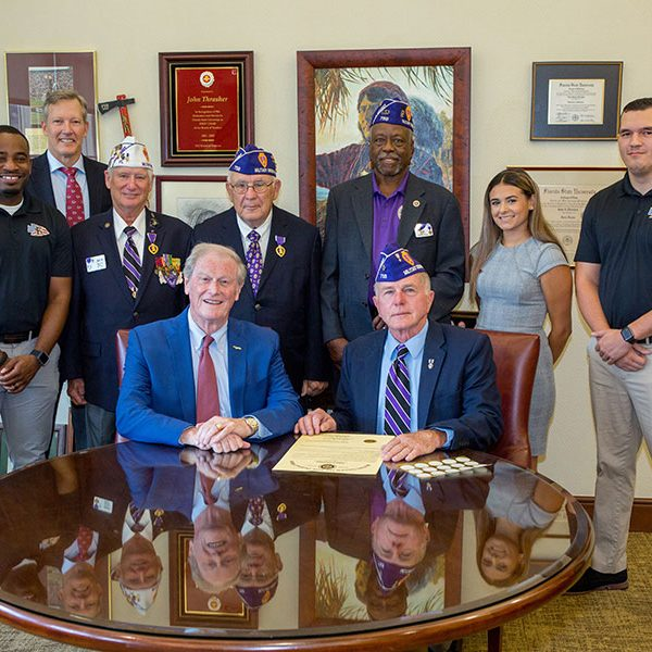 Seated, from left: FSU President John Thrasher and Rick Stanford, commander of the Tallahassee chapter of the Military Order of the Purple Heart. Standing, from left: Sean Williams, director of the FSU Veterans Student Union; Billy Francis, director of the Student Veterans Center; MOH chapter members Ken Swords, Mike Ford and Ned Hill; VSU assistant director Aaliyah Abarzua; and Matt Caraway, treasurer of the FSU Collegiate Veterans Association.
