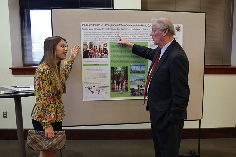 Senior Serena Viola Corson explains her research on longevity and contentment in Italy to FSU President John Thrasher. (Bayard Stern)